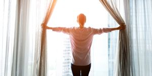 Woman opening curtains and looking out