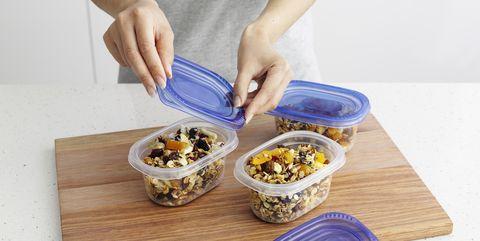 Woman packing granola in tupperware