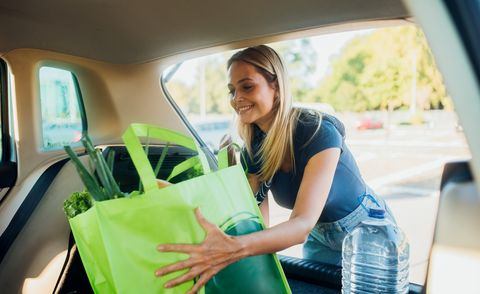 woman packing shopping bags full of groceries into the car trunk