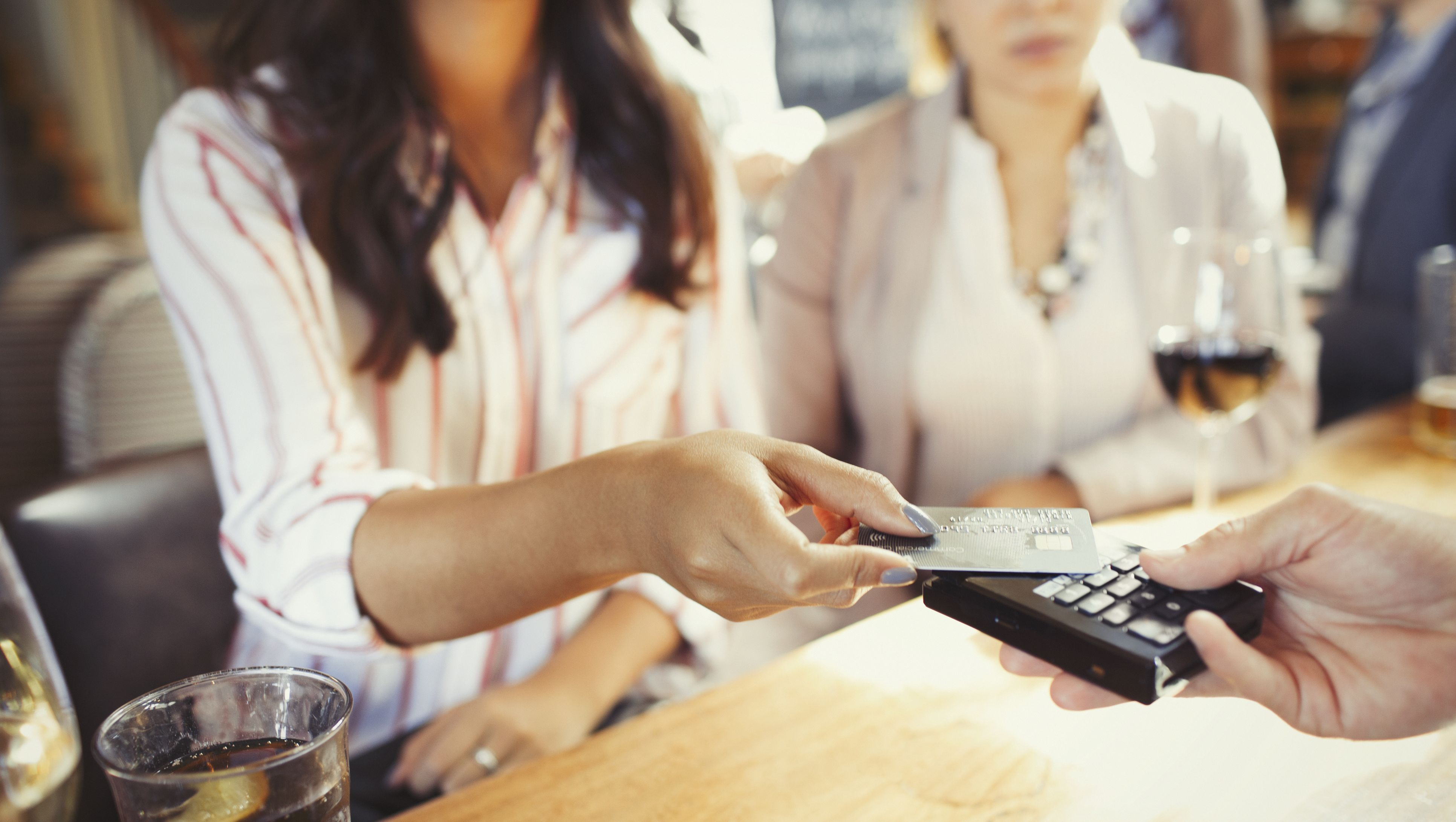 Woman paying bartender with credit card contactless payment at bar