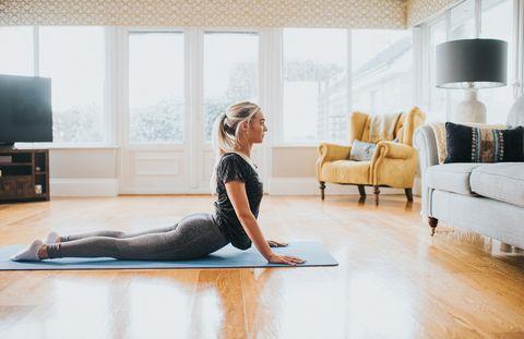 woman performing cobra stretch on a yoga mat