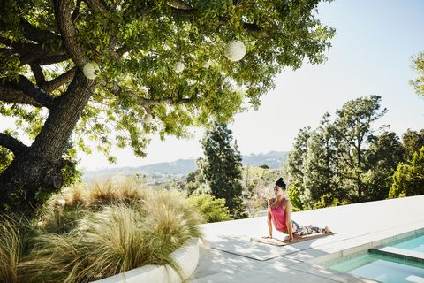woman performing yoga on pool deck of home