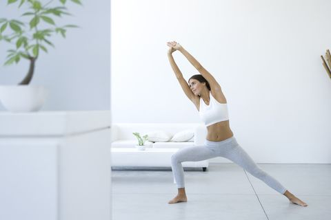 Woman performing yoga pose in living room