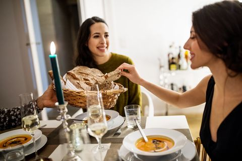 woman picking up bread from basket held by friend during dinner party