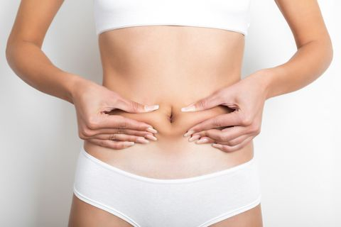 woman pinching her stomach on white background