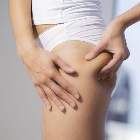 woman pinching thigh, close up