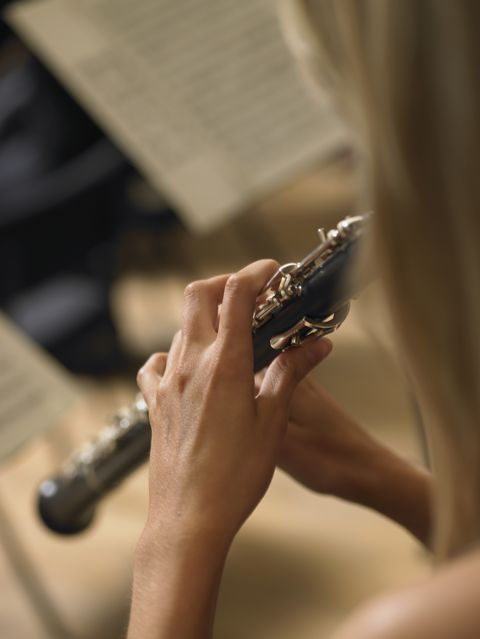 woman playing oboe in orchestra, close up, rear view
