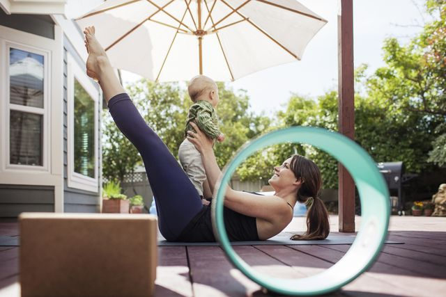 woman playing with baby while doing yoga at backyard