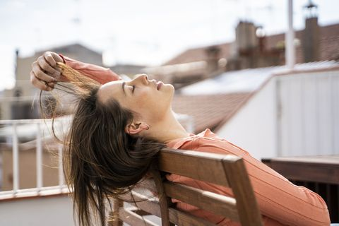 woman playing with hair while relaxing on chair at rooftop