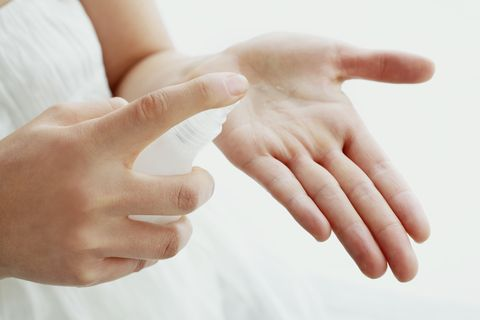 Woman pouring lotion into hand, close-up