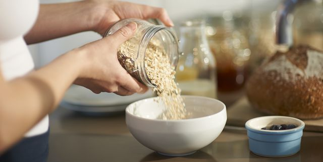 woman pouring oats into bowl in kitchen, close up