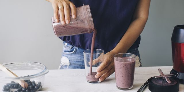 woman pouring smoothie into glasses