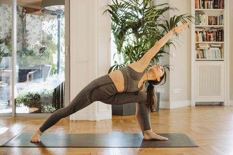 woman practicing extended side angle pose on mat at home