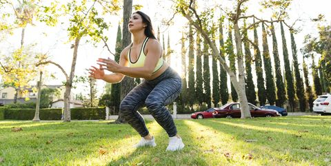 woman practicing jump squats in park