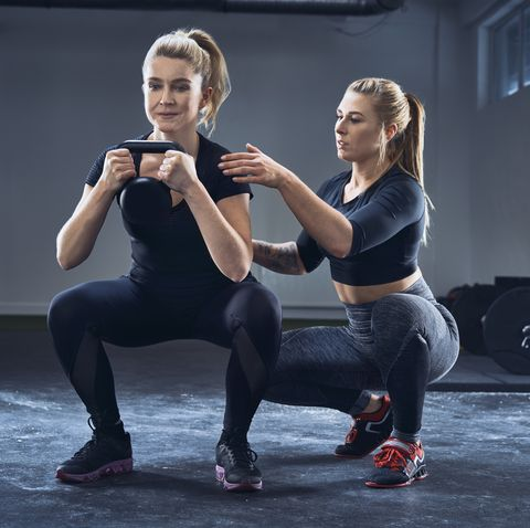 woman practicing kettlebell squat with personal trainer at gym