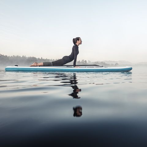woman practicing paddle board yoga on lake kirchsee in the morning, bad toelz, bavaria, germany