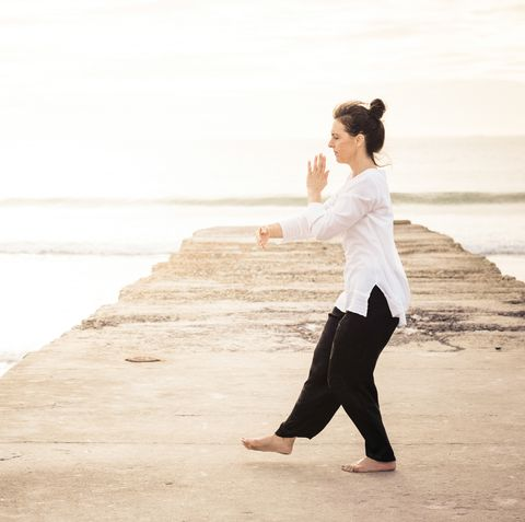 Woman practicing Wu Tai Chi full frame on the end of a concrete pier sunset behind