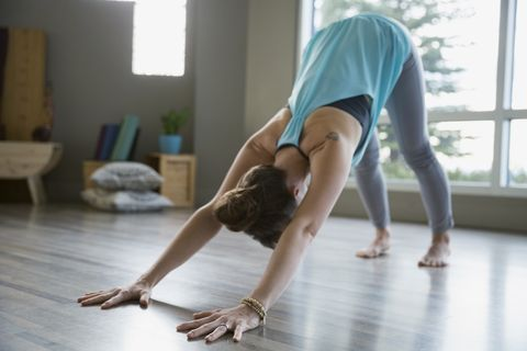 Woman practicing yoga in downward facing dog pose