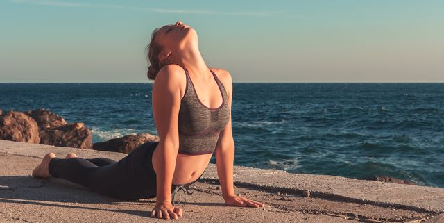 woman practicing yoga in the morning with beautiful sea