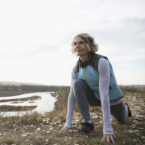 Woman practicing yoga low lunge on autumn hilltop overlooking lake