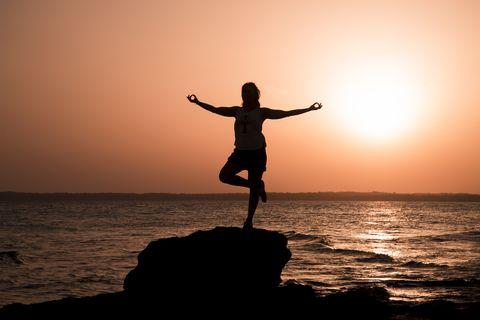 Mujer practicando yoga en una playa de Formentera frente al mar Mediterráneo.