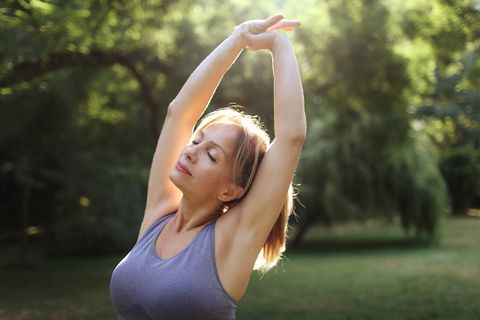 a woman praticing yoga in a park