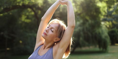 a woman praticing yoga in a park