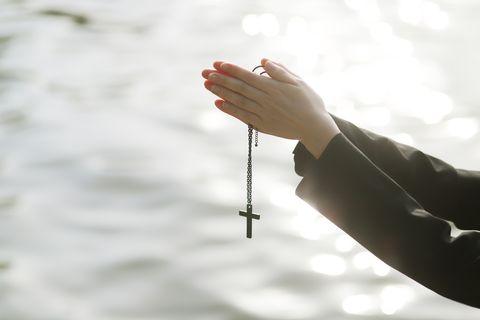 woman praying with cross