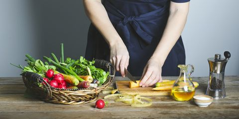 Woman preparing healthy food and cutting fresh carrots on wooden board