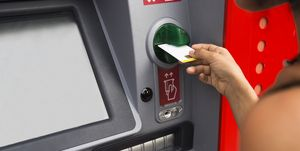 Woman putting debit card into at ATM machine