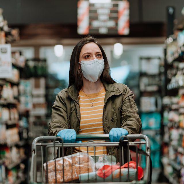 woman pushing supermarket cart during covid 19