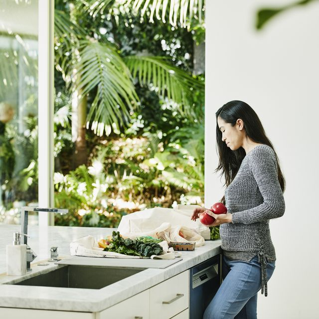 woman putting away groceries in kitchen after shopping