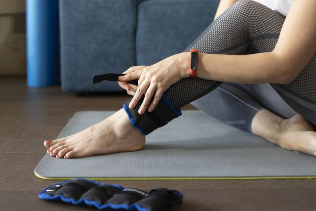 exercising at home woman putting on ankle weights for a home workout