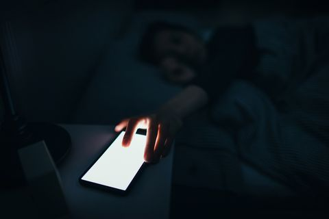 Woman reaching and switching off disturbing calls from work on smartphone while sleeping at midnight