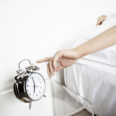 woman reaching to turn off alarm clock