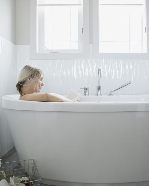Woman reading and relaxing in bathtub