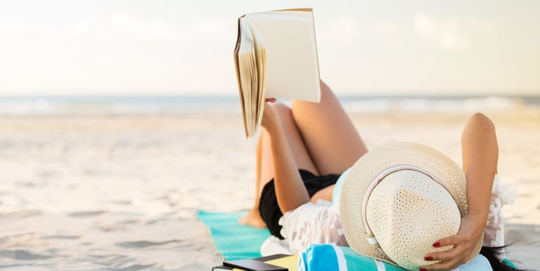 Woman reading book at beach