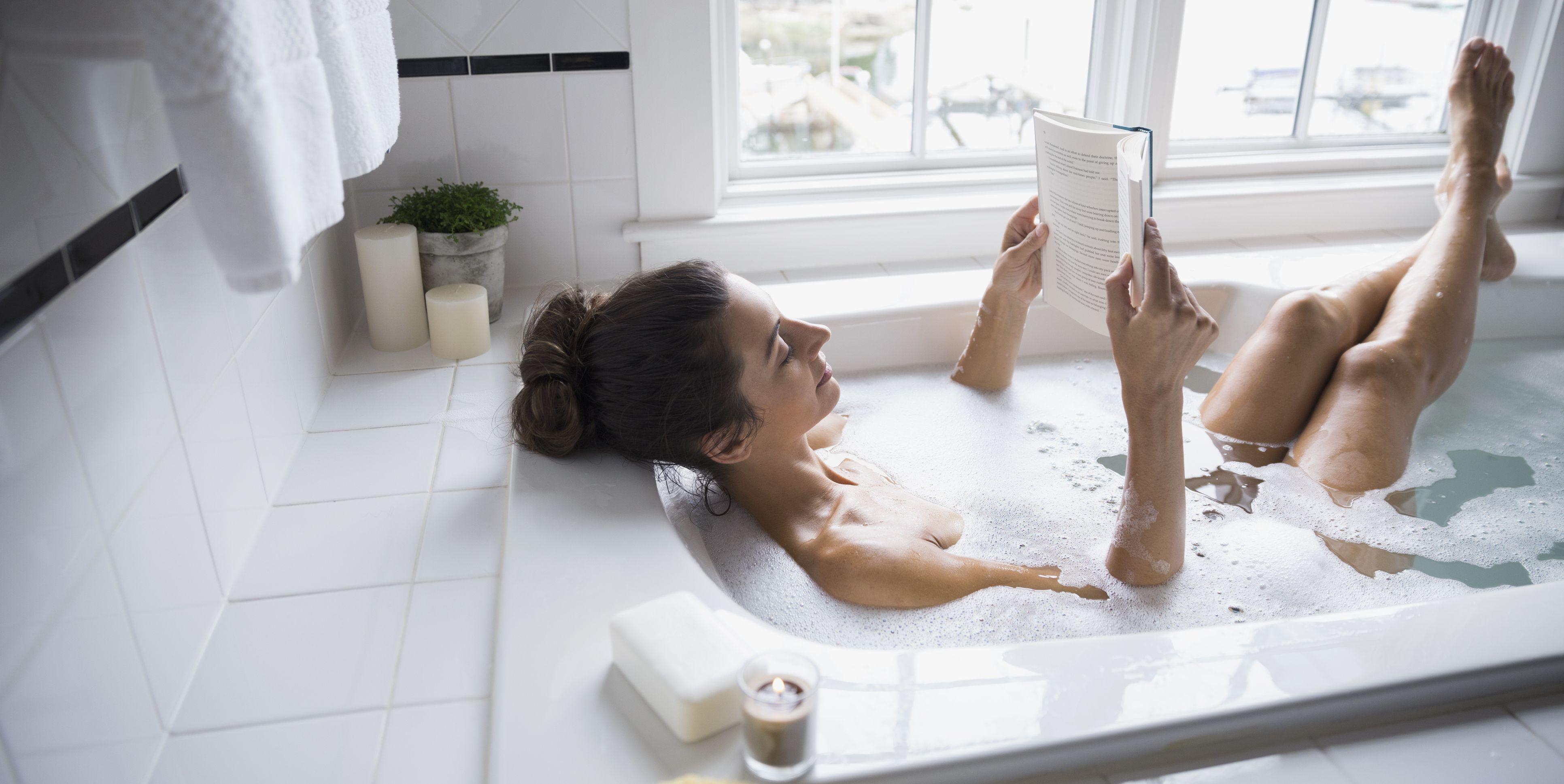 Woman reading book in bubble bath