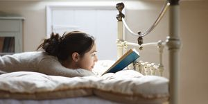 Woman reading book on bed.
