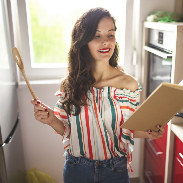 woman reading cookbook and cooking