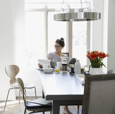 Woman reading newspaper at breakfast dining table