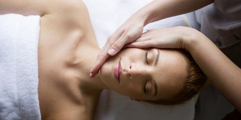 Woman receiving massage from female therapist in spa