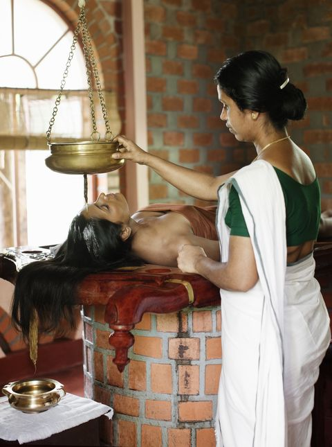 woman receiving shirodhara ayurvedic treatment