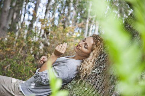 mujer reclinada en un árbol en el bosque
