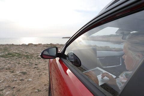 woman relaxes in car near edge of sea