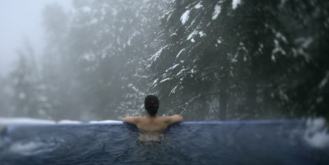 Woman relaxes in outdoor spa.
