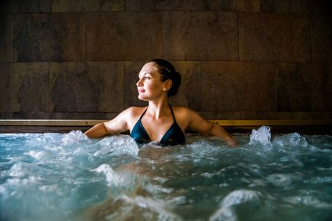 Woman relaxing in a jacuzzi pool during weekend days of relax and spa in a luxury place during travel vacations.