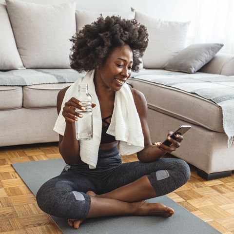 woman resting after home workout with water and phone