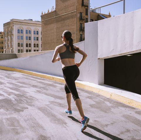 woman runner climbing parking garage in city