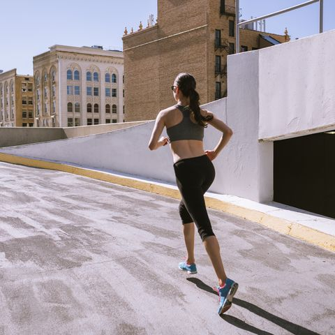 woman runner climbing parking garage in city